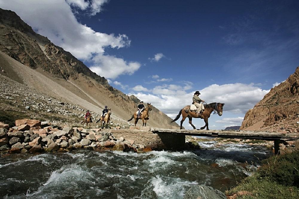 Horseback riders crossing bridge over river