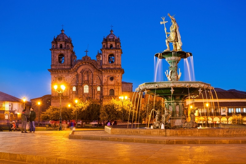 Dusk photo of Cusco Cathedral, with Inca on top of a fountain.