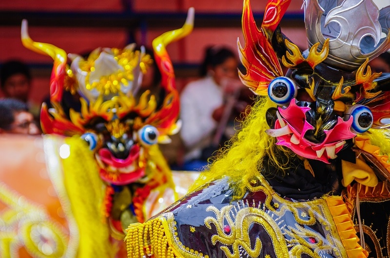 two devil type characters in bright colors dancing in candelaria festical Puno Peru.