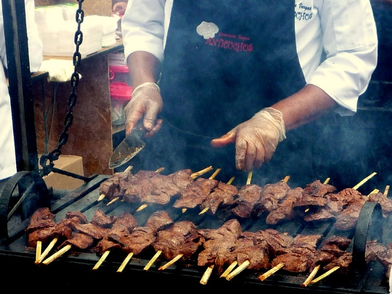 Chef cooking anticuchos on outside grill