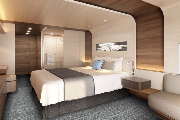 Cruise ship cabin in white with grey carpets showcasing the bed