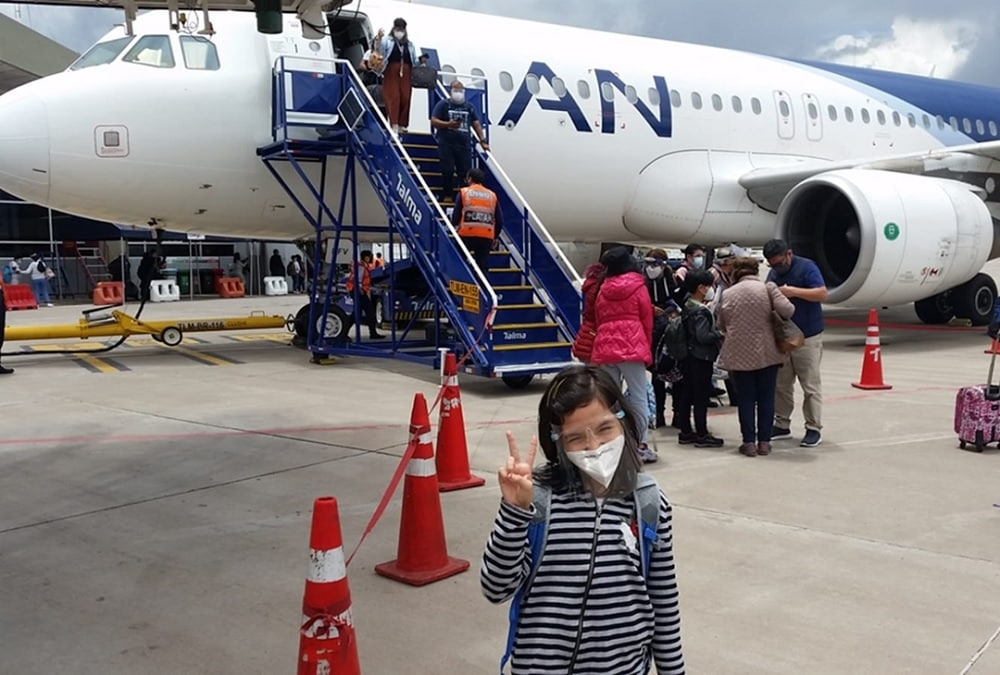little girl with face mask and shield boarding an aircraft.